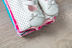 Folded pink and white bodysuit with shoes on it  grey wooden background. diaper for newborn girl. Stack of infant clothing. Child Stock Images