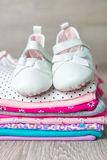 Folded pink and white bodysuit with shoes on it  grey wooden background. diaper for newborn girl. Stack of infant clothing. Child Stock Photos