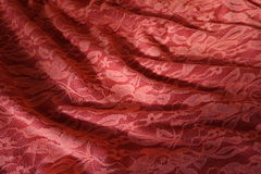 Folded pinkish orange guipure cloth with shadows Royalty Free Stock Photos