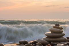 Stack of zen stones on beach. Folded pyramid Zen pebble stones on the sea beach at sunset Royalty Free Stock Photos