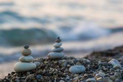 Stack of zen stones on pebble beach. Folded pyramid Zen pebble stones on the sea beach at sunset royalty free stock photo