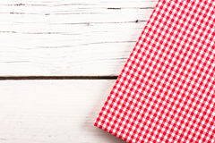 Folded red checkered tablecloth on white wooden board Stock Photography