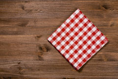 Folded red-white napkin on wooden table Stock Images