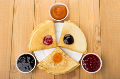 Folded russian pancakes in plate and bowls with different jam Stock Photos