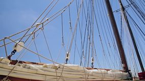 Folded sail and rigging of a sailboat against the sky. Folded sail and rigging of a sailboat stock video footage