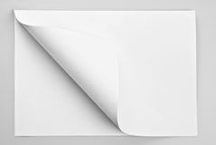 Folded sheet of paper with curled corner stock image