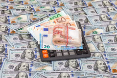 Folded stack of russian roubles, euro banknotes and calculator Royalty Free Stock Photos