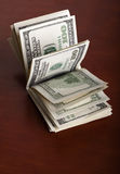 Folded 100 US$  Bills Stack on Brown Background Stock Photo