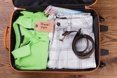 Folded summer apparel and belt. Travel tips, flat lay. Male clothes in suitcase Royalty Free Stock Photos