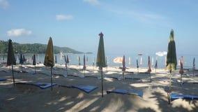 Folded sun umbrellas on Patong beach in the morning. Phuket, Thailand. Clip stock video