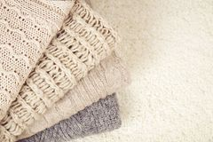 Folded sweaters gradient on white rug Royalty Free Stock Photography