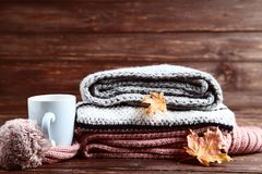 Sweaters, scarf with cup and leafs. Folded sweaters, scarf with cup and maple leafs on wooden background royalty free stock images