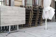 Folded tables and chairs of a street cafe stand on the sidewalk royalty free stock image