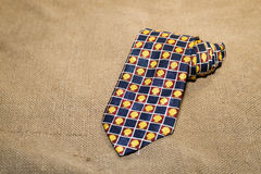 Folded  tie with a cheerful pattern on the old tissue Royalty Free Stock Image