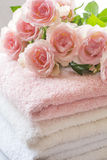 Folded towels and pink roses. Folded towels on bathroom counter with ligh pink roses Royalty Free Stock Photos