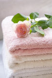 Folded towels and pink roses. Folded towels on bathroom counter with ligh pink roses Stock Photography