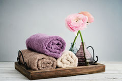 Folded towels with ranunculus Stock Photography