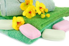Towel, soaps and flowers. Folded towels, soaps and flowers closeup picture Royalty Free Stock Photo