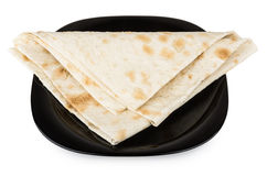 Folded triangle of thin Armenian lavash in black glass plate Royalty Free Stock Photos