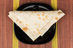 Folded triangle of thin Armenian lavash in black plate on mat Royalty Free Stock Image
