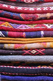 Folded Turkish carpets. A closeup of a pile of neatly folded, colorful Turkish carpets royalty free stock image