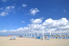 Folded umbrellas and chairs on beautiful beach Marina di Vecchiano nearby Pisa in Italy Royalty Free Stock Photo
