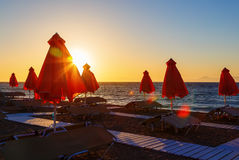 Folded umbrellas and sunbeds on the background of the setting sun of Rhodes Greece stock photography