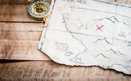 Folded Vintage fake map of abstract island and red cross of Treasure chest on wooden table. Fake treasure map with compass Stock Photography