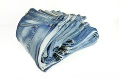 Folded washed-out blue jeans. Stack of washed-out folded blue jeans isolated on white Royalty Free Stock Photos