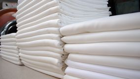 Folded white cloths in a laundry stock photo