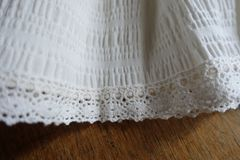 Folded white fabric with lace on wood Royalty Free Stock Photography