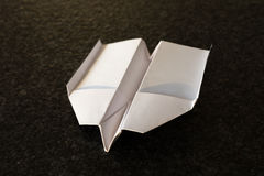 Folded white paper plane on a black background Royalty Free Stock Photo