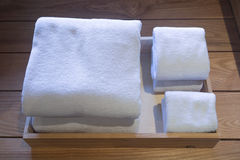 Folded white towels in a wooden tray. Different sizes of folded white towels in a wooden tray Stock Photo