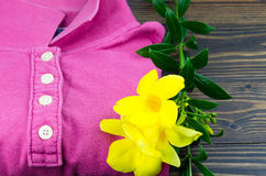 A folded women washed t-shirt with yellow flora decorated on wooden background Stock Photos