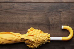 Folded yellow umbrella on the table Stock Photo