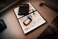 Folder with the charts of financial analysis. Diagrams in the phone`s screen, next is calculator and pen Stock Photo