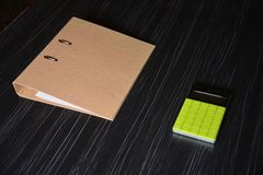 Folder with a green calculator on the black table. Brown folder with a green calculator on the black office table Stock Photo