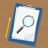 Folder, magnifier and pencil. Folder with clip and paper, magnifying glass and a pencil lying on a wooden table Royalty Free Stock Photos