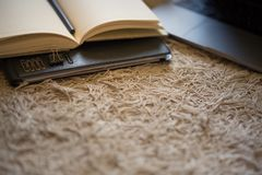 Folder, open notebook, stationary and laptop on a textured rug royalty free stock images