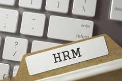 Folder Register with Inscription HRM. 3D. HRM written on  Sort Index Card on Background of Modern Laptop Keyboard. Business Concept. Closeup View. Toned Blurred Stock Photos
