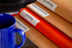Folder stack on a desktop with a cup of coffee Stock Photos