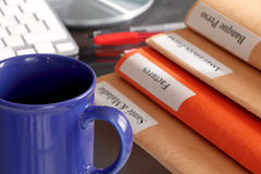 Folder stack on a desktop with keyboard and a coffee cup Stock Images
