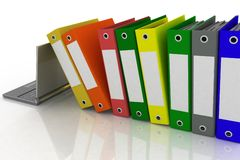 Folders  and laptop. Colorful folders next to a modern laptop Royalty Free Stock Photo