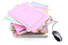 Folders with laptop and Mouse. Isolated stack of folder with laptop computer and a mouse shot over white background Royalty Free Stock Images