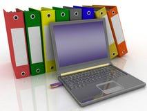 Folders and modern laptop. Colorful folders next to a modern laptop Stock Photo