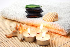 Foldet white bath towel and zen stones. Towel and zen stones showing a bath or wellness concept Stock Photos