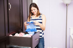Folding baby clothes in a closet. Attractive young pregnant brunette folding and storing baby clothes on a closet in a nursery before the baby's arrival Stock Photos