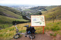 Folding bicycle near walking trail information plate Stock Photos