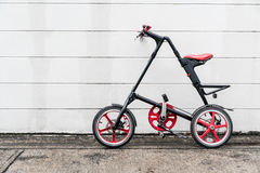 Folding bike black & red. Black and red folding bicycle in front of white concrete wall Royalty Free Stock Photos