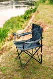 Folding black chair for fishing and outdoor relaxation. On the river lake Royalty Free Stock Photo